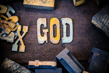 jehovah: The word GOD written in rusted metal letters surrounded by vintage wooden and metal letterpress type.