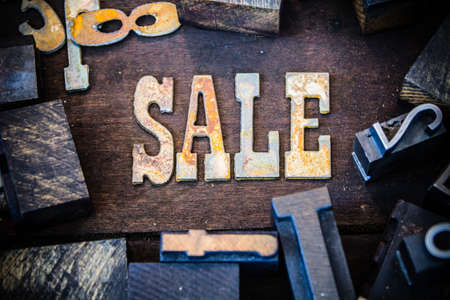 The word SALE written in rusted metal letters surrounded by vintage wooden and metal letterpress type. photo