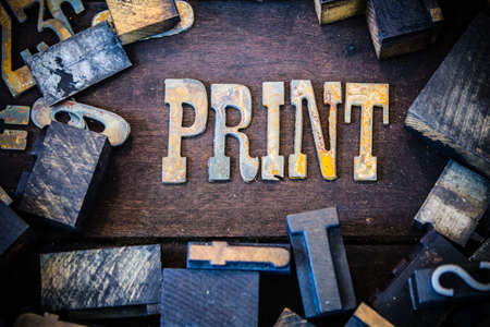 The word PRINT written in rusted metal letters surrounded by vintage wooden and metal letterpress type. photo