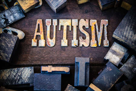 The word AUTISM written in rusted metal letters surrounded by vintage wooden and metal letterpress type. photo
