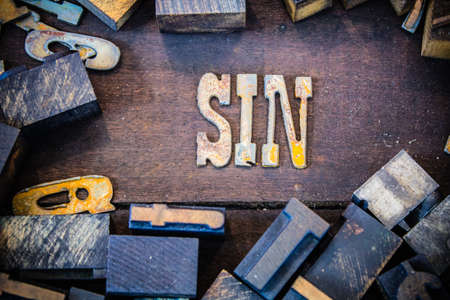 unlawful act: The word SIN written in rusted metal letters surrounded by vintage wooden and metal letterpress type. Stock Photo