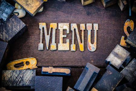 Het woord menu geschreven in verroeste metalen letters omgeven door vintage houten en metalen boekdruk type. Stockfoto