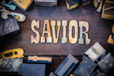 The word SAVIOR written in rusted metal letters surrounded by vintage wooden and metal letterpress type. Stock Photo