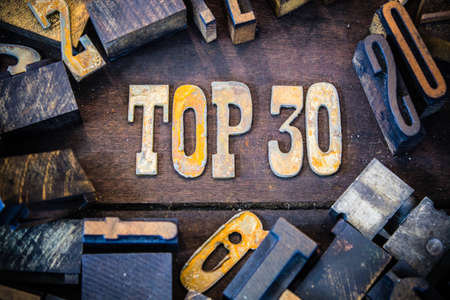 letterpress words: The words TOP 30 written in rusted metal letters surrounded by vintage wooden and metal letterpress type. Stock Photo