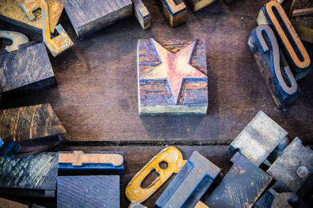 printmaker: A vintage letterpress star surrounded by wooden and rusted metal letters and numbers in a dirty wooden print tray. Stock Photo