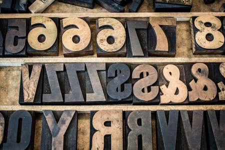 letterpress letters: A vintage drawer of old wooden letterpress letters, numbers, and symbols. Type is ink stained and photographed with the letters naturally backwards as they normally appear before printing.