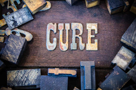 The word CURE written in rusted metal letters surrounded by vintage wooden and metal letterpress type.