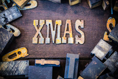 letterpress letters: The word XMAS written in rusted metal letters surrounded by vintage wooden and metal letterpress type.