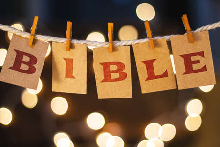 printmaking: The word BIBLE printed on clothespin clipped cards in front of defocused glowing lights. Stock Photo