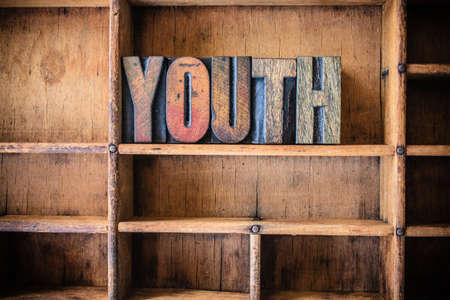 youth background: The word YOUTH written in vintage wooden letterpress type in a wooden type drawer. Stock Photo