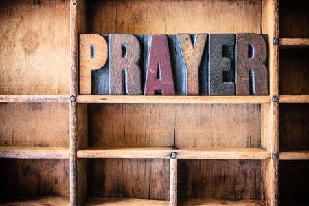 letterpress words: The word PRAYER written in vintage wooden letterpress type in a wooden type drawer.