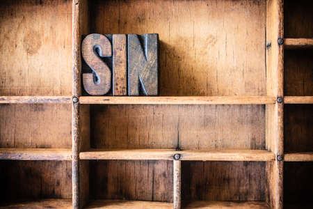 sinful: The word SIN written in vintage wooden letterpress type in a wooden type drawer.