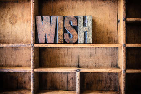 The word WISH written in vintage wooden letterpress type in a wooden type drawer. Stock Photo