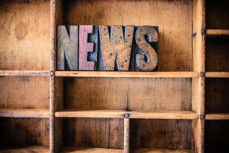 letterpress letters: The word NEWS written in vintage wooden letterpress type in a wooden type drawer.