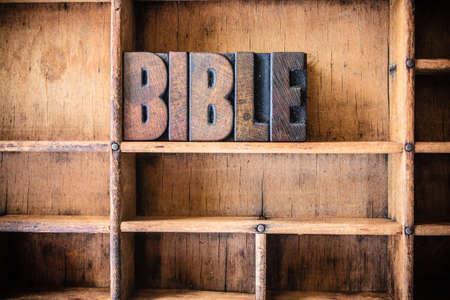 devotional: The word BIBLE written in vintage wooden letterpress type in a wooden type drawer.