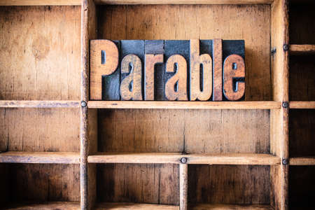The word PARABLE written in vintage wooden letterpress type in a wooden type drawer. photo