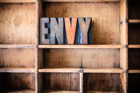 envious: The word ENVY written in vintage wooden letterpress type in a wooden type drawer.
