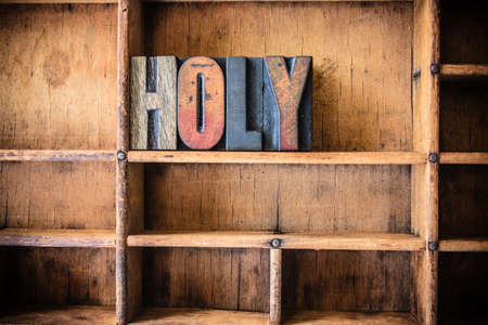 sanctified: The word HOLY written in vintage wooden letterpress type in a wooden type drawer. Stock Photo