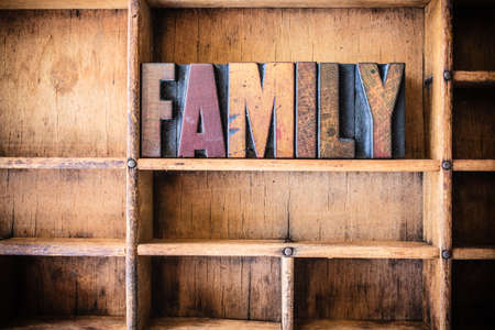 The word FAMILY written in vintage wooden letterpress type in a wooden type drawer.