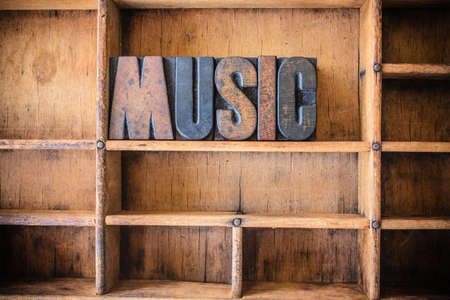 hymn: The word MUSIC written in vintage wooden letterpress type in a wooden type drawer.