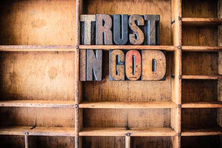 De woorden vertrouwen in God geschreven in oldtimers houten letterpress type in een houten soort lade. Stockfoto - 40232785