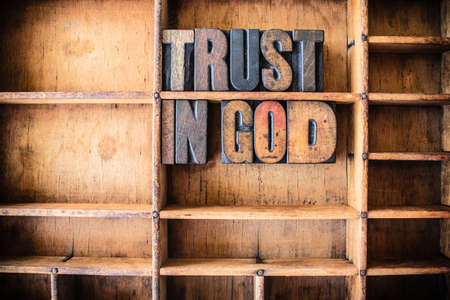 The words TRUST IN GOD written in vintage wooden letterpress type in a wooden type drawer.
