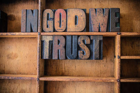 in god we trust: The phrase IN GOD WE TRUST written in vintage wooden letterpress type in a wooden type drawer.