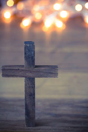 catholic: A wooden Christian cross with a soft bokeh lights background.