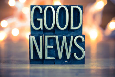 letterpress words: The words GOOD NEWS written in vintage metal letterpress type on a soft backlit background.
