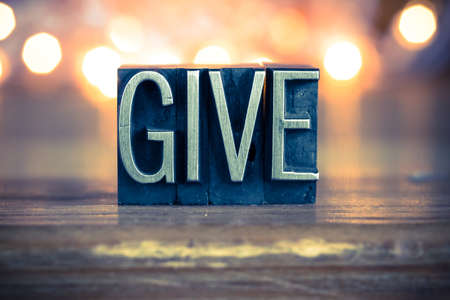 The word GIVE written in vintage metal letterpress type on a soft backlit background.