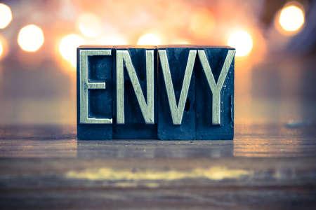 The word ENVY written in vintage metal letterpress type on a soft backlit background.