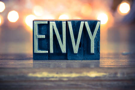 envious: The word ENVY written in vintage metal letterpress type on a soft backlit background.