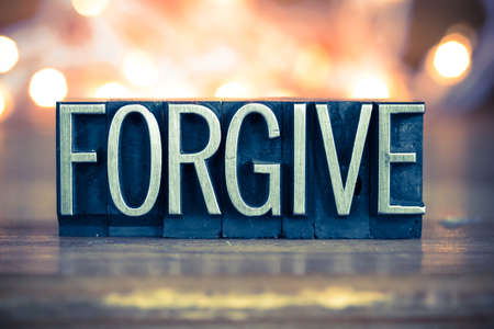 The word FORGIVE written in vintage metal letterpress type on a soft backlit background.
