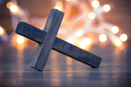 christian symbol: A wooden Christian cross with a soft bokeh lights background.