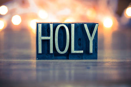 The word HOLY written in vintage metal letterpress type on a soft backlit background. Stock Photo