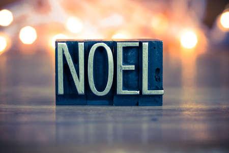 ballad: The word NOEL written in vintage metal letterpress type on a soft backlit background.
