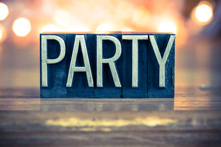 The word PARTY written in vintage metal letterpress type on a soft backlit background. Stock Photo