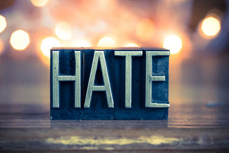 grievance: The word HATE written in vintage metal letterpress type on a soft backlit background.