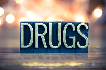 illegal drugs: The word DRUGS written in vintage metal letterpress type on a soft backlit background.
