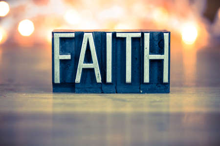 The word FAITH written in vintage metal letterpress type on a soft backlit background.