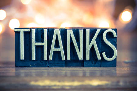 thanks you: The word THANKS written in vintage metal letterpress type on a soft backlit background.