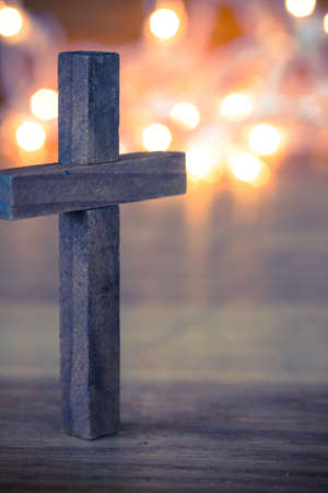 A wooden Christian cross with a soft bokeh lights background.