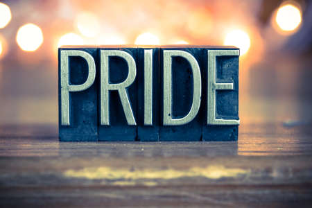 The word PRIDE written in vintage metal letterpress type on a soft backlit background. Stock Photo