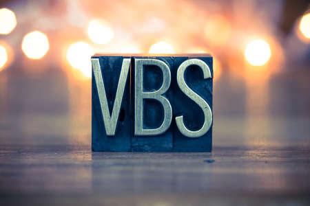 The word VBS written in vintage metal letterpress type on a soft backlit background. Banque d'images