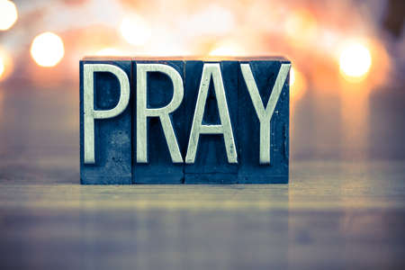 The word PRAY written in vintage metal letterpress type on a soft backlit background.