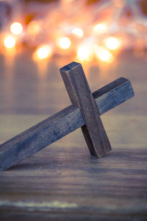 prayers: A wooden Christian cross with a soft bokeh lights background.