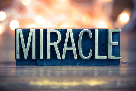 parable: The word MIRACLE written in vintage metal letterpress type on a soft backlit background. Stock Photo