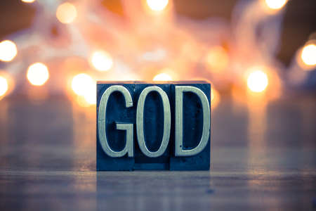 The word GOD written in vintage metal letterpress type on a soft backlit background.