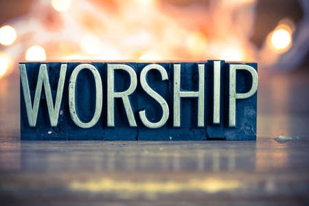 The word WORSHIP written in vintage metal letterpress type on a soft backlit background.