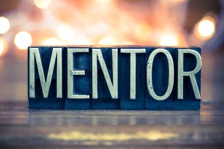 The word MENTOR written in vintage metal letterpress type on a soft backlit background. 스톡 콘텐츠